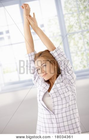 Young attractive woman getting up, stretching in the morning in pyjama.? poster