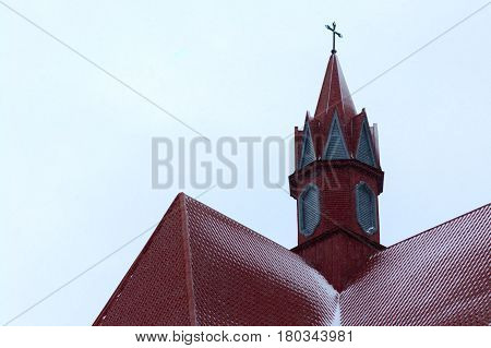 The roof of the modern Catholic Church tower with a cross. Winter. Snowing. Ukraine. Berezhany. Location: 49°26'37.5