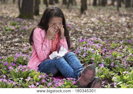Allergic girl rubbing her eyes sitting in the wood