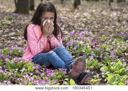 Cute girl blowing her nose among primroses