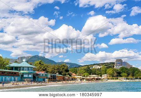 ALUSHTA, RUSSIA - MAY 15, 2016: Tourists sunbathe and swim at the beach. Alushta is a well-known resort in Crimea.