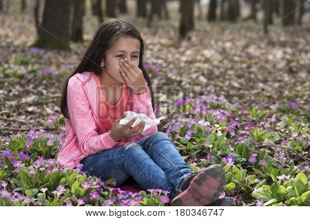 Girl sitting among primroses and sneezing holding tissue