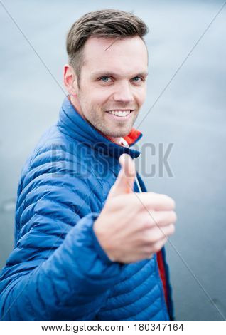 Portrait of an attractive young man showing thumbs up.