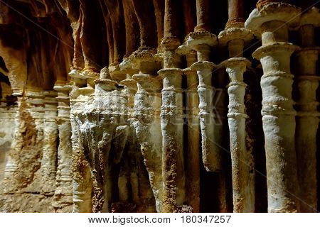 Stalagmites and stalactites in a karst cave. Tubular cave formations. Background.