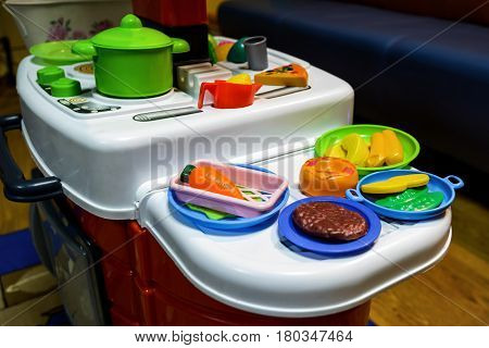 Children's toy kitchen with toy food in playroom