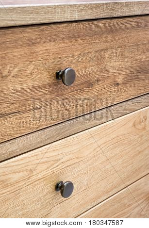 A natural wooden furniture detail with drawers