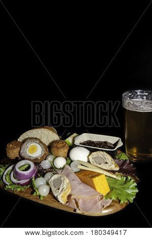 Traditional English pub grub  meal of a ploughman's lunch served with a pint of lager. The typical cold food includes pork pies ham hard boiled eggs and cheese with salad. Isolated against a black background with copy space.
