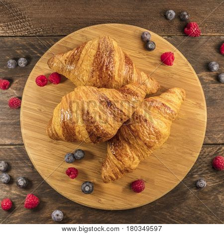 A square shot of crunchy French croissants with fresh raspberries and blueberries on a wooden cutting board with copy space