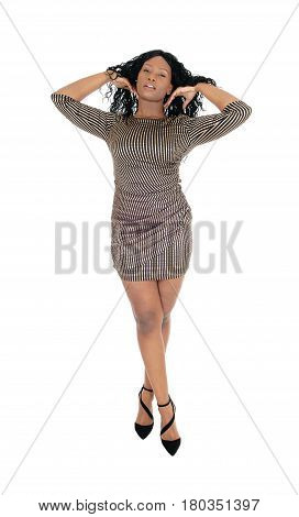 A beautiful African American woman standing in a short dress with her legs crossed isolated for white background.
