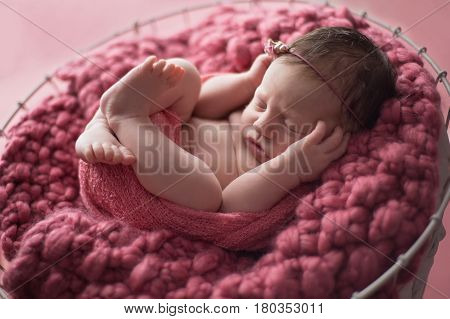 Nine day old newborn baby girl swaddled and sleeping in a wire basket lined with a dusty pink knit blanket.
