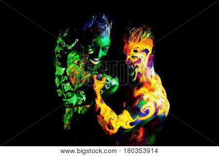 Body art glowing in ultraviolet light, four elements, Land against Fire