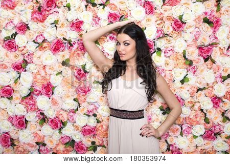 Closeup portrait of a beautiful young brunette woman in a studio on a floral wall background