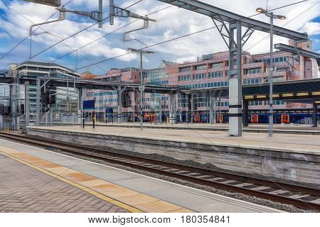 Urban mainline station with overhead live electric wires on a bright sunny day