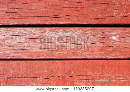 A fragment of a wall paneled with red painted threadbare wooden planks