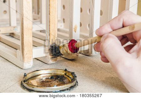 hand holding a brush applying varnish paint on a wooden surface