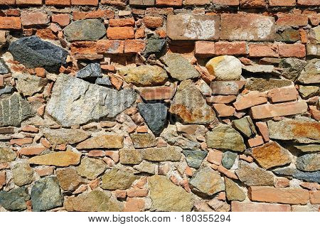A rough wall made of different colored uneven stones