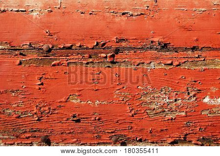 Red painted cracked wooden plank with rusty tacks