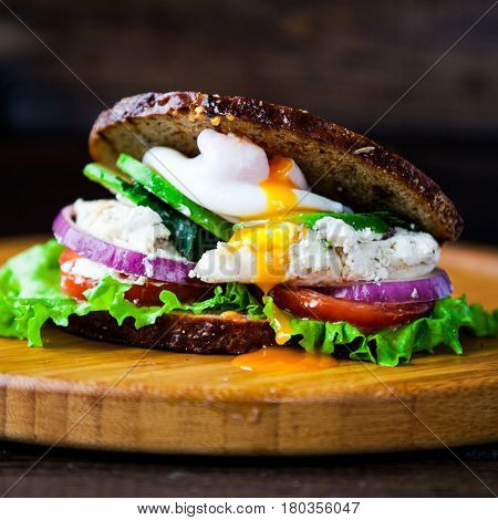 Fresh homemade sandwich with cereals dark rye grain bread, salad lettuce, avocado, tomato, grilled chicken breast, curd cheese, poached egg and greengrocery on wooden table. Healthy lifestyle breakfast.