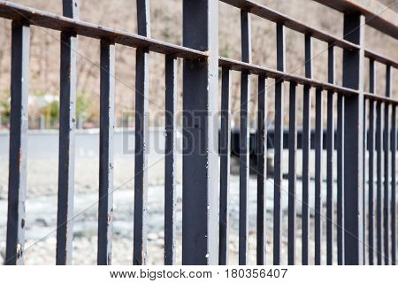 Rusty old black metal railing of a bridge over river. Iron fence.