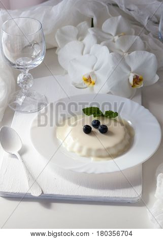 Delicious tasty Italian dessert Panna Cotta with fresh blueberries and mint leaves on a white plate. Served with vine glasses, white tea spoon and orchid flowers for decoration. Wedding menu