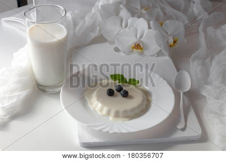 Delicious tasty Italian dessert Panna Cotta with fresh blueberries and mint leaves on a white plate. Served with  glass of milk, white tea spoon and orchid flowers. Wedding menu