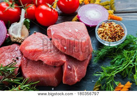 Raw meat beef steaks slices ready for roasting on a black slate stone board over wooden table with fresh organic vegetables, onion, garlic, spices, peppercorns, rosemary, sea salt, cherry tomatoes, macaroni, dill, parsley and herbs. Top view
