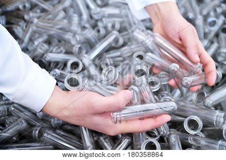 Plastic billets for the production of pvc bottles in the hands of men. Industrial production of transparent polyethylene containers