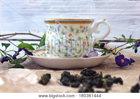 Cup Of Green Tea Milk Oolong And Scattered Cones For Brewing On The Wooden Table