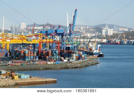 Container terminal in the seaport. Unloading cargo ships in dock.  Cranes and containers on the harbour. Business life is the seaside city of port Vladivostok - Golden horn Bay.