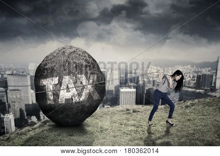 Young businesswoman climbing a hill while pulling a big stone with a Tax word. Concept of big Tax