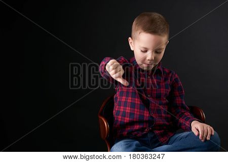 Close up emotional portrait of caucasian unhappy little cute boy giving thumbs down hand gesture. Angry child looking with disapproval facial expression isolated on black background. Negative human face
