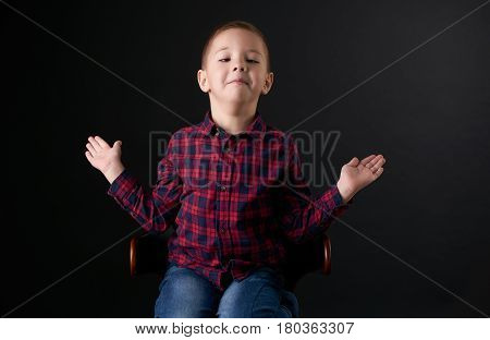 Close-up portrait of a Little boy with a stupid emotion shrugs shoulders I do not know isolated on black wall background. Human emotion facial expression.