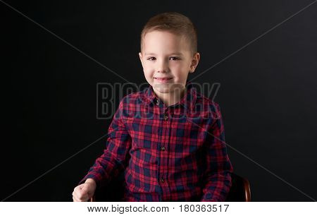 Close-up portrait of a Cute smiling boy in a red plaid shirt sitting on wooden chair isolated on black background. Human emotion facial expression.