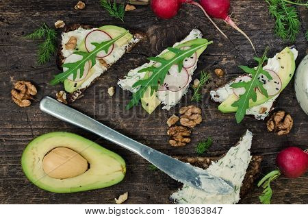 Sandwiches with avocado radish arugula cheese and nuts on a rye bread with sunflower seeds on wooden board on dark background. Healthy breakfast. Vegetarian food. Top view.