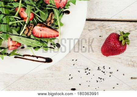 Fresh salad with arugula strawberries nuts black sesame seeds and balsamic glasse sauce served on white plate on rustic wooden table. Healthy organic diet food concept. Top view.