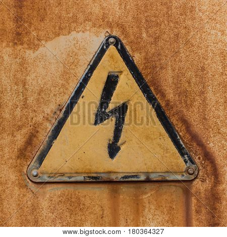 Old triangular High Voltage sign attached by rivets to a sheet of rusty iron.