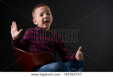 A close-up portrait of a cute young winking boy with a one eye closed showing his tongue dressed in a fashionable plaid shirt and jeans sitting on a chair on a black background. Boy blond welcomes with a thumb up.