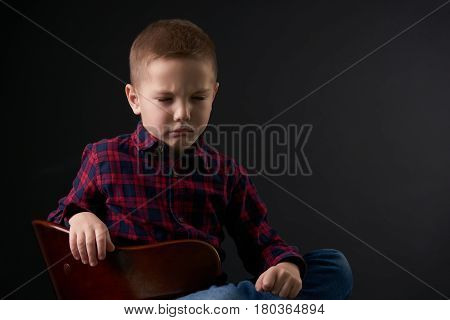 Close-up portrait of a Cute young offended boy with closed eyes sits on the chair against black background. Human emotion facial expression.