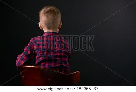 Close-up portrait of Cute young little Offended boy in plaid shirt turned away sits on the chair in front of a black background. Human emotion facial expression.