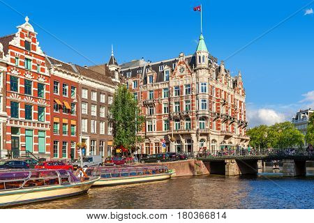 AMSTERDAM, NETHERLANDS - JULY 07, 2015: Cruise boats and typical buildings of Amsterdam - capital city of Netherlands, popular tourist destination with more than 5 million visitors annually.