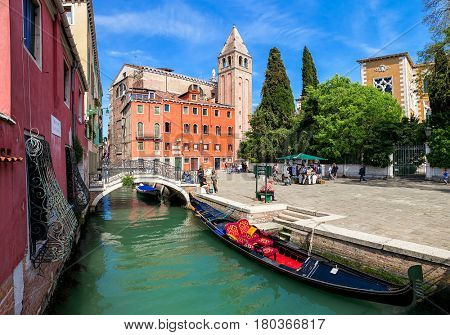 VENICE, ITALY - APRIL 21, 2016: Gondola on canal and small town square in Venice - one of the famous and beautiful cities in the world, popular tourist destinations.