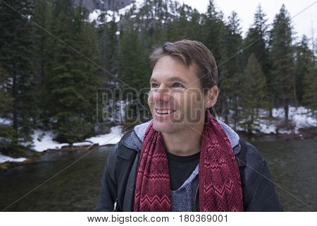Handsome blonde Caucasian man smiling amidst a wonderful winter backdrop of river pines and snowy mountains
