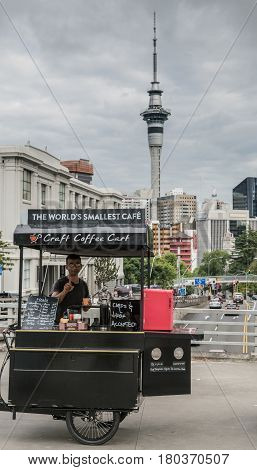Auckland New Zealand - March 1 2017: Tricycle craft coffee shop claiming to be the smallest one in the world. Owner barista. On Symonds/Wellesley overpass. Sky Tower high rises and cloudy sky.