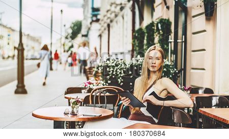 Amateur charming blonde woman surfing internet via digital tablet while sitting in street cafe alone pensive beautiful lady having online chat on her touch pad on sunny summer day in bar outdoors