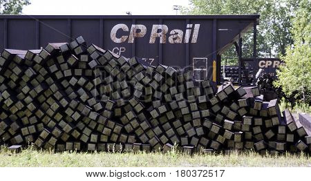 Montreal, Quebec, August 20, 2016 - Close up view of a train container car beside a large pile of railroad ties in the CP Rail Train Yards in Cote Saint Luc in Montreal, Quebec, on a sunny day in August.