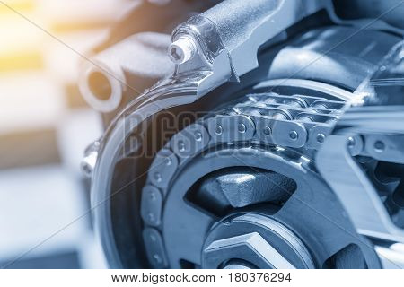 The drive chain of motorcycle in light blue scene with lighting effect.