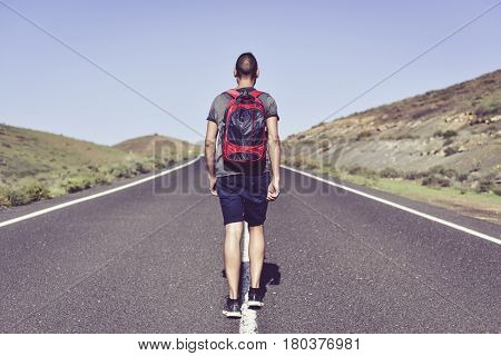 closeup of a young caucasian man seen from behind carrying a backpack walking by the centerline of a minor road