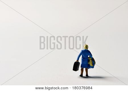 miniature traveler woman seen from behind carrying some suitcases on an off-white background with a large blank space on the left