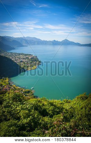 An elevated view over the sparkling blue water, the majestic mountains and a small town on a lake in Guatemala.