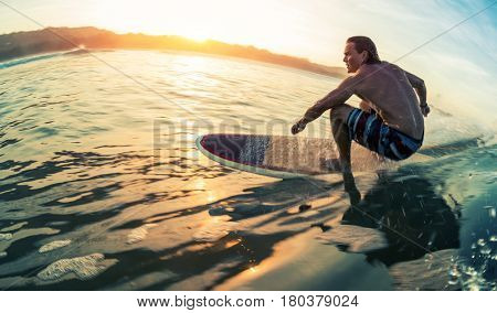 Young man surfs the ocean wave at calm sunrise